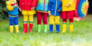 Kids in rain boots. Rubber boots for children. Kids in rain boots. Group of kindergarten children in colorful rubber boots and autumn jackets. Footwear for Royalty Free Stock Images