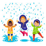 Kids in raincoats and rubber boots playing Royalty Free Stock Image