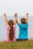 Kids with raised arms. Young caucasian kids in Denmark on a summer day Royalty Free Stock Photo