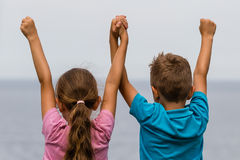 Kids with raised arms. Young caucasian kids in Denmark on a summer day Royalty Free Stock Photography