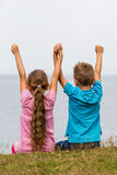 Kids with raised arms. Young caucasian kids in Denmark on a summer day Royalty Free Stock Photos