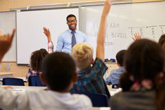 Kids raising hands to answer in an elementary school class royalty free stock photography