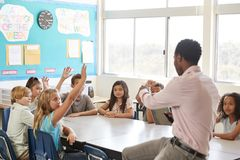 Kids raising hands to answer in an elementary school lesson royalty free stock photos