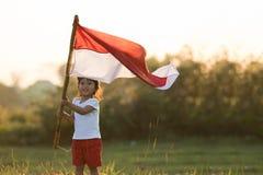 Free Kids Raising Indonesian Flag Royalty Free Stock Photos - 122176138
