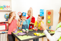 Kids raising their hands up at road safety lesson Royalty Free Stock Images
