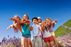 Kids reaching out their hands to camera outdoors Royalty Free Stock Images