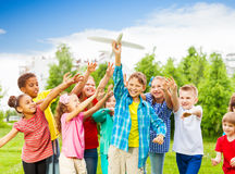 Kids reaching after white airplane toy with arms Stock Images