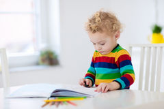 Kids read, write and paint. Child doing homework. Cute little boy doing homework, reading a book, coloring pages, writing and painting. Children paint. Kids Stock Photo