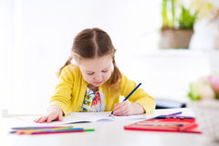 Kids read, write and paint. Child doing homework. Cute little girl doing homework, reading a book, coloring pages, writing and painting. Children paint. Kids royalty free stock image