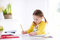 Kids read, write and paint. Child doing homework. Cute little girl doing homework, reading a book, coloring pages, writing and painting. Children paint. Kids royalty free stock photos