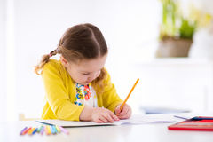 Kids read, write and paint. Child doing homework. Cute little girl doing homework, reading a book, coloring pages, writing and painting. Children paint. Kids Royalty Free Stock Images