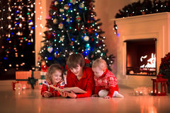 Kids reading a book on Christmas eve at fireplace. Children read a book and open gifts at fireplace on Christmas eve. Family with child celebrating Xmas Stock Photos