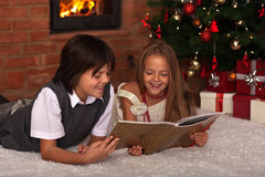 Kids reading a book - in front of the Christmas tree Stock Photo