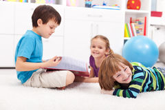 Kids reading a book and having fun Stock Photography