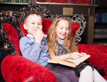 Kids reading book at home Stock Photography
