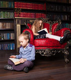 Kids reading book at home Stock Images