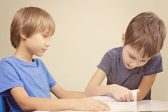 Kids reading a book. Little boy practice reading with his brother. Royalty Free Stock Image