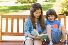 Kids reading book on park bench Royalty Free Stock Photos