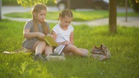 Kids reading a book in summer garden. Preschool friends playing and learning. Girls doing their homework. stock video