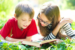 Kids reading a book. Kids reading together enjoying a book laying on the grass outdoors