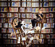 Kids Reading Books in Fantasy Library. Two children are reading books on long, surreal wooden chairs in a library with books and papers flying around them for an Stock Image