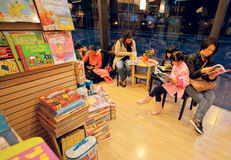 Kids reading the new books in a bookstore of large shopping mall royalty free stock images
