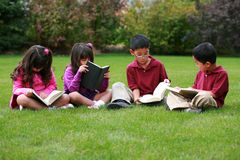 Kids Reading Outside Royalty Free Stock Photos