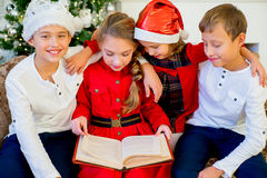 Kids reading a story book on Christmas time Stock Photography