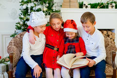 Kids reading a story book on Christmas time. Kids reading a story book together under a Christmas tree on Christmas time at home Royalty Free Stock Photography