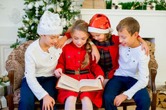 Kids reading a story book on Christmas time. Kids reading a story book together under a Christmas tree on Christmas time at home Royalty Free Stock Photos