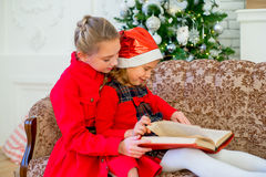 Kids reading a story book on Christmas time. Kids reading a story book together under a Christmas tree on Christmas time at home Stock Image