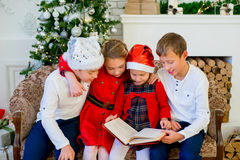 Kids reading a story book on Christmas time. Kids reading a story book together under a Christmas tree on Christmas time at home Royalty Free Stock Photo