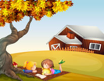 Kids reading under a big tree Stock Photo