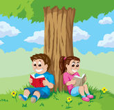 Kids reading under a tree Royalty Free Stock Photos
