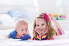Kids reading in white bedroom Royalty Free Stock Photography