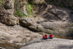 Kids red sandals on a rock near a river Stock Photography