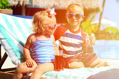 Kids relax on tropical beach resort and drink. Juices, family vacation Stock Photo