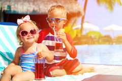 Kids relax on tropical beach resort and drink. Juices, family vacation Stock Images
