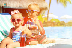 Kids relax on tropical beach resort and drink juices. Family vacation Royalty Free Stock Images