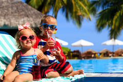 Kids relax on tropical beach resort and drink juices Stock Image