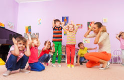 Kids repeat after teacher making ears with hands. Group of kids repeat after teacher in kindergarten class holding hands making big ears stock photos
