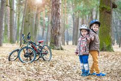 Kids resting after biking. Happy and fun moments of leasure time on bikes in forest Royalty Free Stock Image