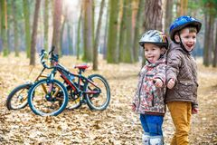 Kids resting after biking. Happy and fun moments of leasure time on bikes in forest Stock Photography