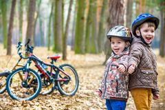 Kids resting after biking. Happy and fun moments of leasure time on bikes in forest Stock Images