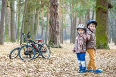 Kids resting after biking warm autumn day. Kids resting after biking happy and fun moments of leasure time on bikes in forest stock photos