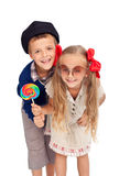 Kids in retro clothes. Happy kids in retro outfit holding huge lollipop - isolated Royalty Free Stock Image