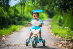 Kids ride baby bycycle Stock Images