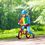 Kids ride balance bike in park Royalty Free Stock Images