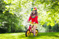 Kids ride balance bike in park. Child riding balance bike. Kids on bicycle in sunny park. Little girl enjoying to ride glider bike on warm summer day Royalty Free Stock Images