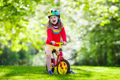 Kids ride balance bike in park Stock Images